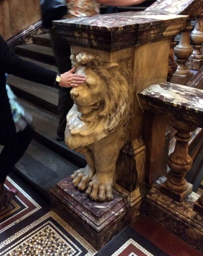 The white marble lion on the stairwell in Glasgow's City Chambers building; from a travel blog by www.traveljunkiegirl.com