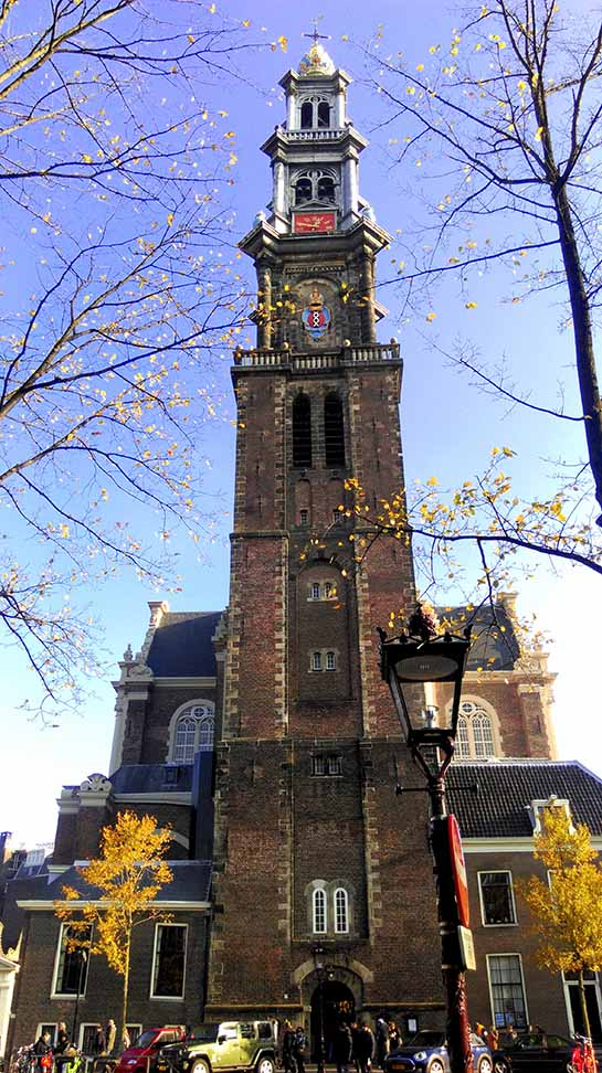 The Westerkerk in Amsterdam set amongst autumn colour; from a travel blog by www.traveljunkiegirl.com