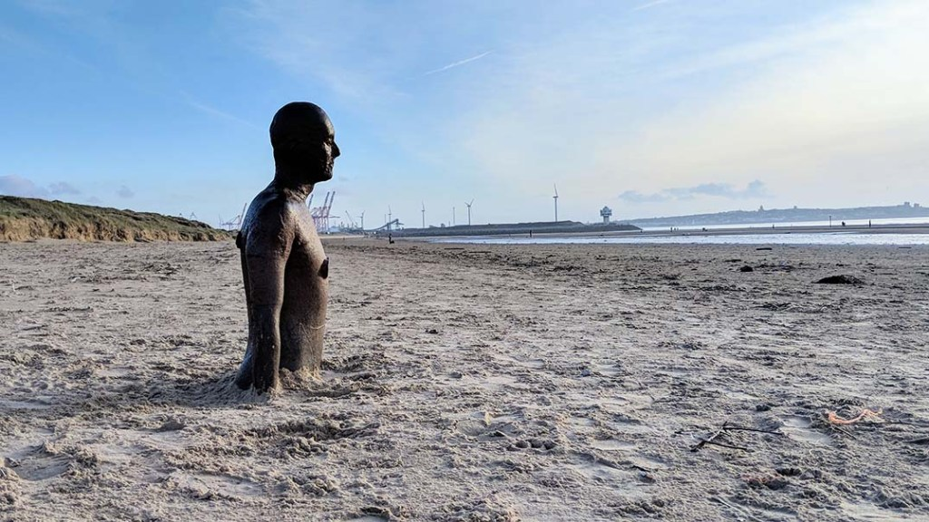 Anthony Gormley's 'Another Place' Iron Men at Crosby Beach, Merseyside - some of the men are sunk into the sand like this one so they look like they're at different levels in the water when the tide is in; from a travel blog by www.traveljunkiegirl.com