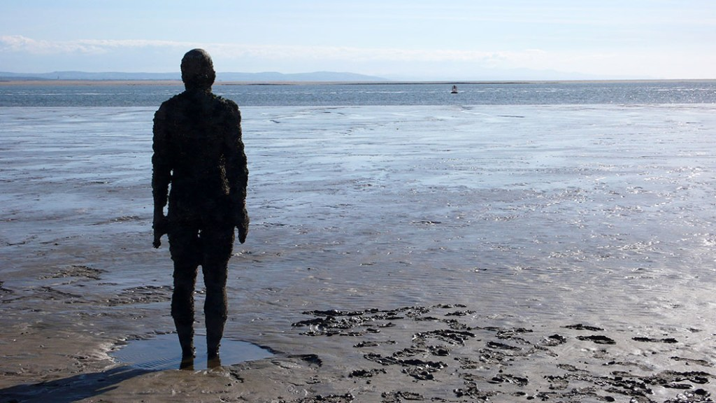 Anthony Gormley's 'Another Place' iron men sculptures on Crosby Beach, Merseyside, looking out to sea and to the Welsh hills beyond; from a travel blog by www.traveljunkiegirl.com