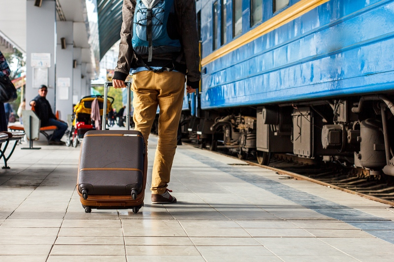 Man boarding train with luggage - Carry-on vs Checked Luggage via @TravelLatte.net
