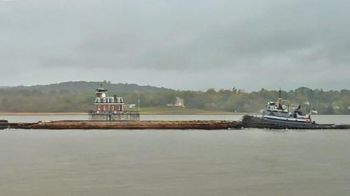 A barge on the Hudson River passes a channel house, as we pass by on the Amtrak Adirondack, by TravelLatte.