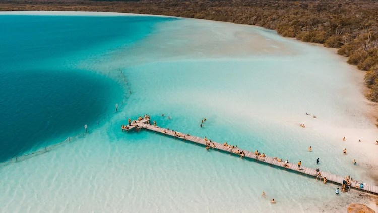 The Kaan Luum lagoon is located in Tulum, Quintana Roo in Mexico. People walk the boardwalk over the lagoon to the cenote.