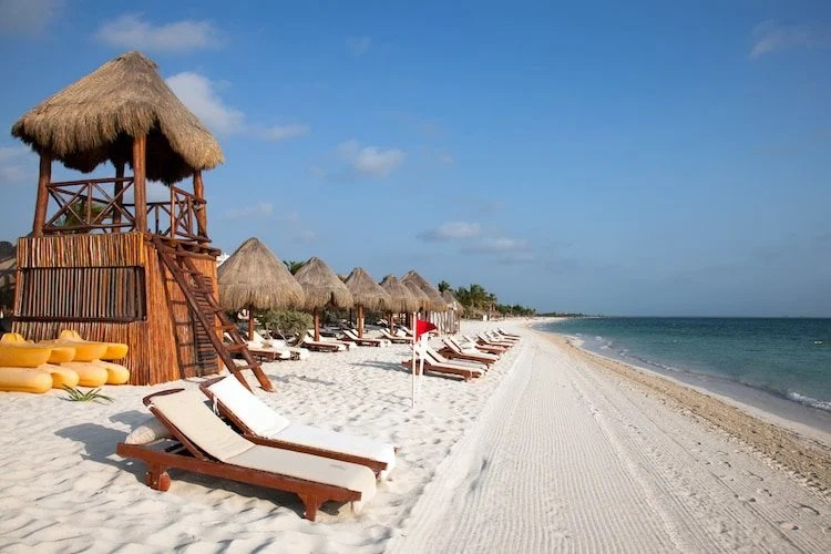 Loungers line the beaches of Playa del Carmen in Mexico, with a lifeguard house