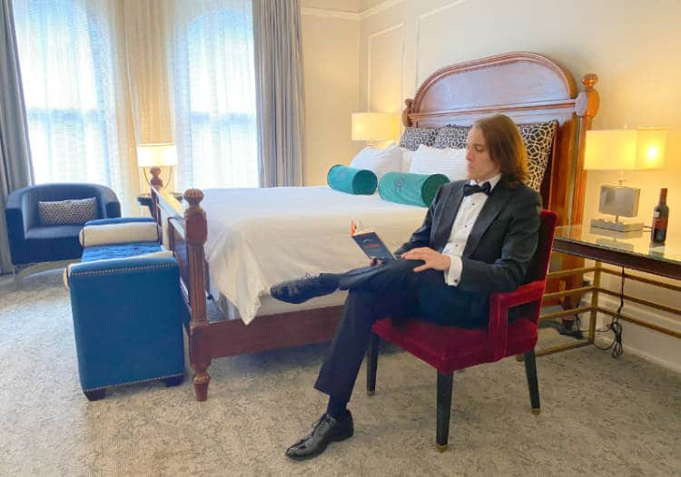 The author reading a book in a chair in a room at the Oxford Hotel