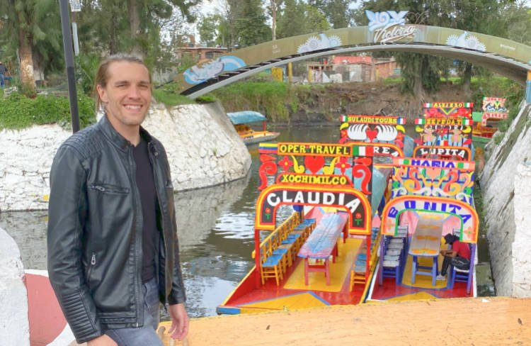 The author in front of colorful boats at Floating Gardens of Xochimilco