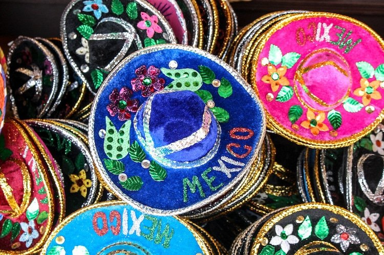 """Piles of colorful velvet hats that say """"Mexico"""" on them in Playa del Carmen, Mexico"""