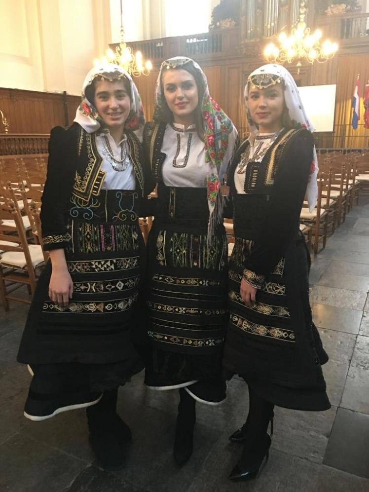 Drie jonge dames in xhubleta's tijdens de viering in Den Haag