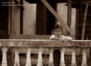 An Acehnese boys waits for his parents by the balcony.