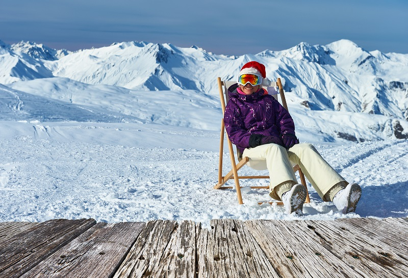 Woman at mountains in Santa hat celebrating christmas, Meribel,