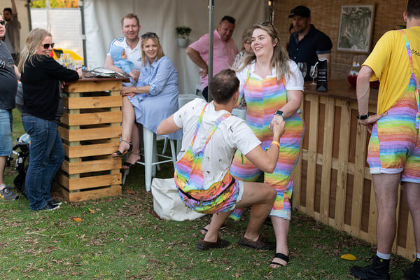 couple-wearing-rainbow-overalls-falling-over
