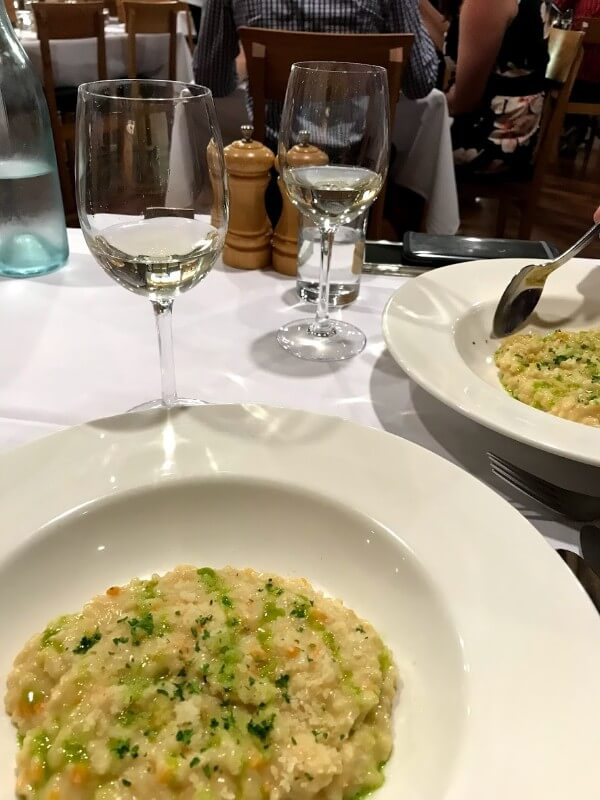 second-course-risotto-con-grano-padano-at-pinelli-estate-winery-restaurant-with-a-glass-of-vermentino-reserve