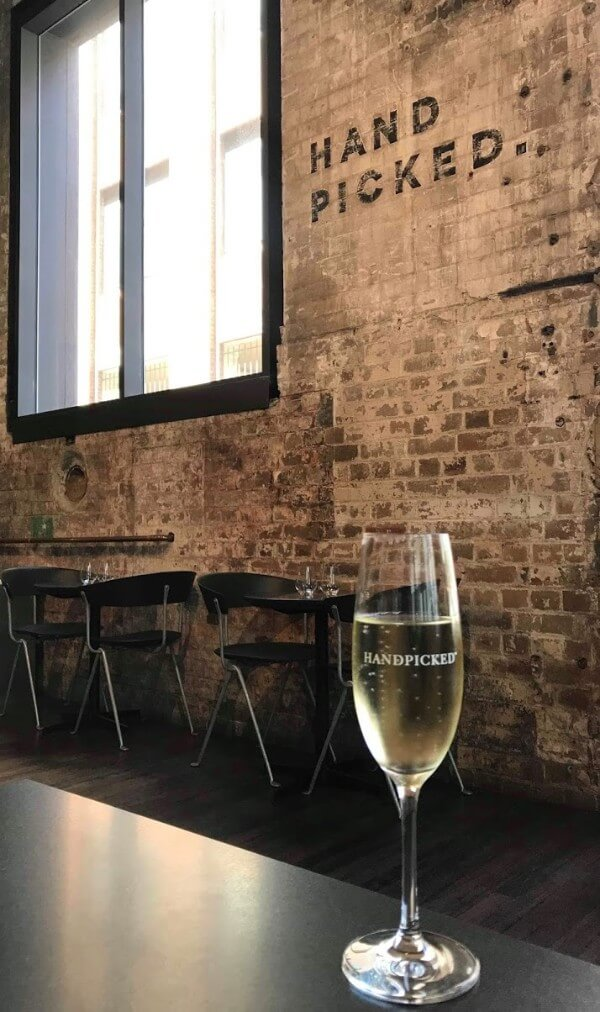 glass of sparkling wine on table against brick wall