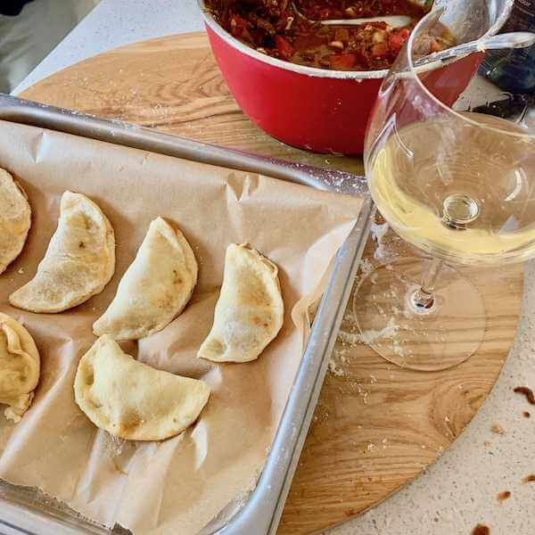 Making empanadas and drinking wine
