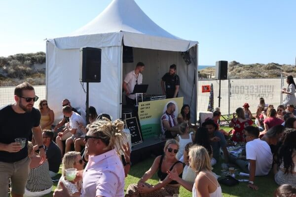 dj booth and people sitting on the grass