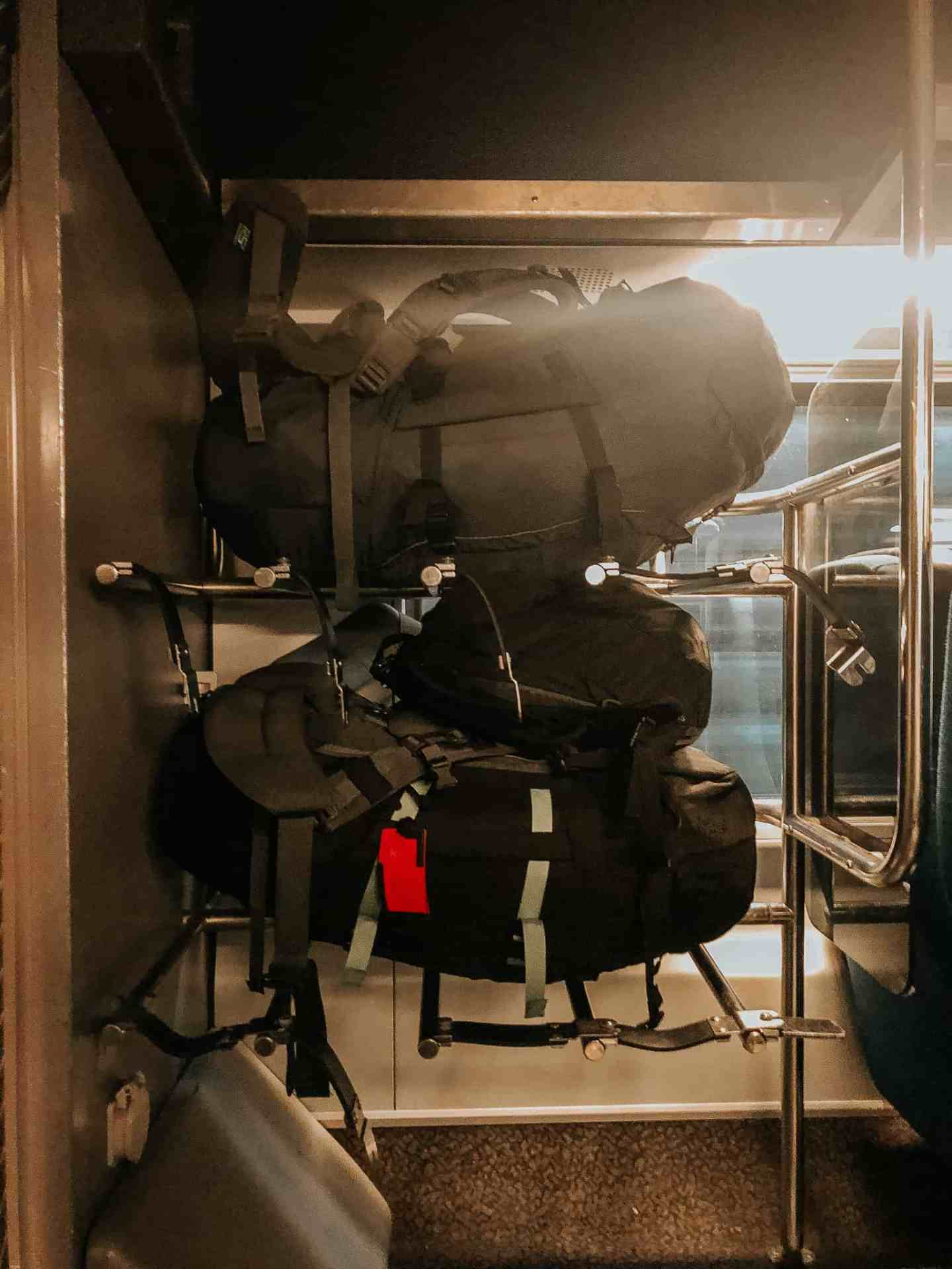 Two large backpacks sitting in a luggage rack