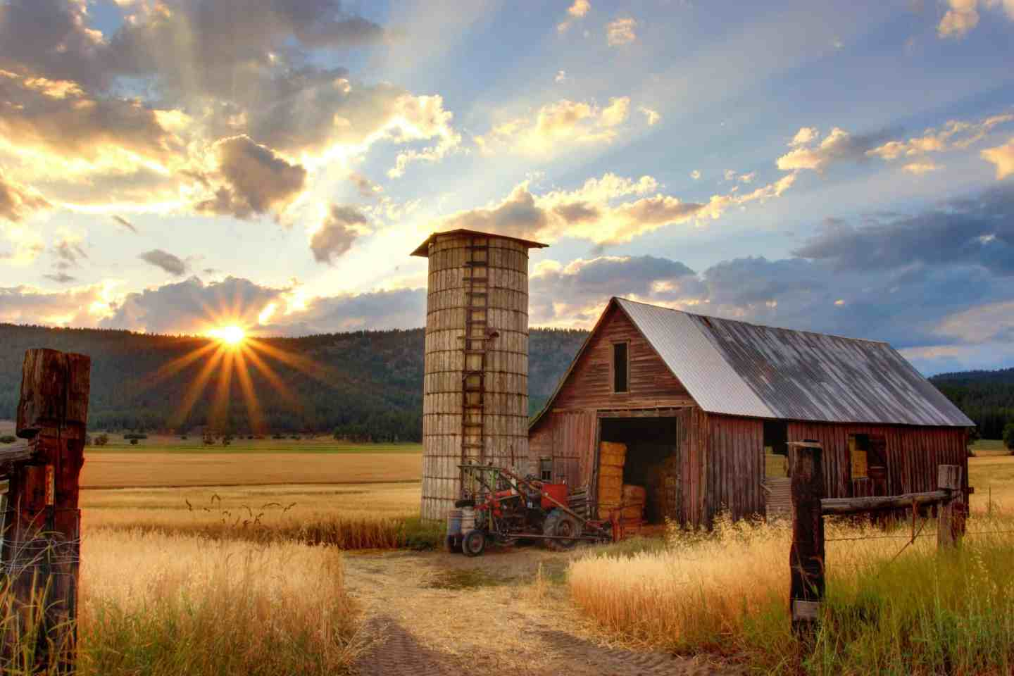 Old farm house with sun setting over the mountain