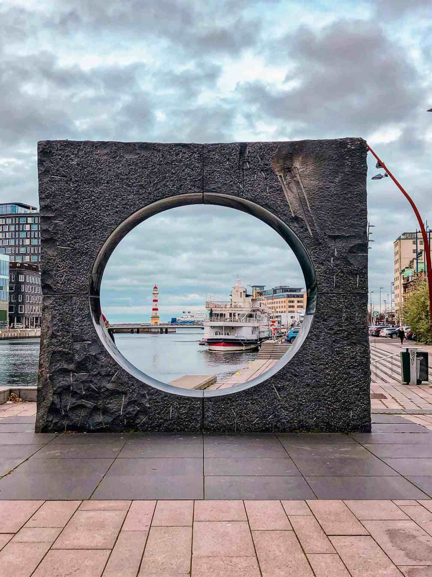 Circle in the middle of a stone square with a boat and lighthouse in the background