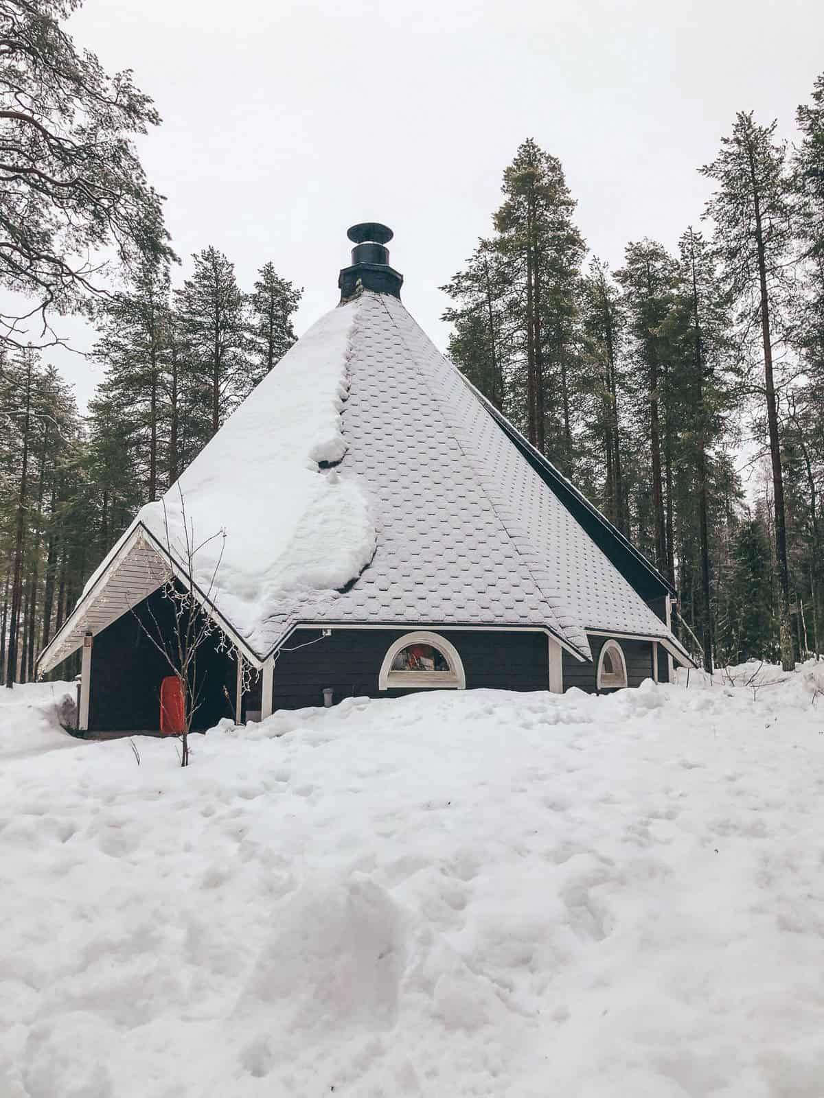 A finnish style hut with a red door surrounded by snow