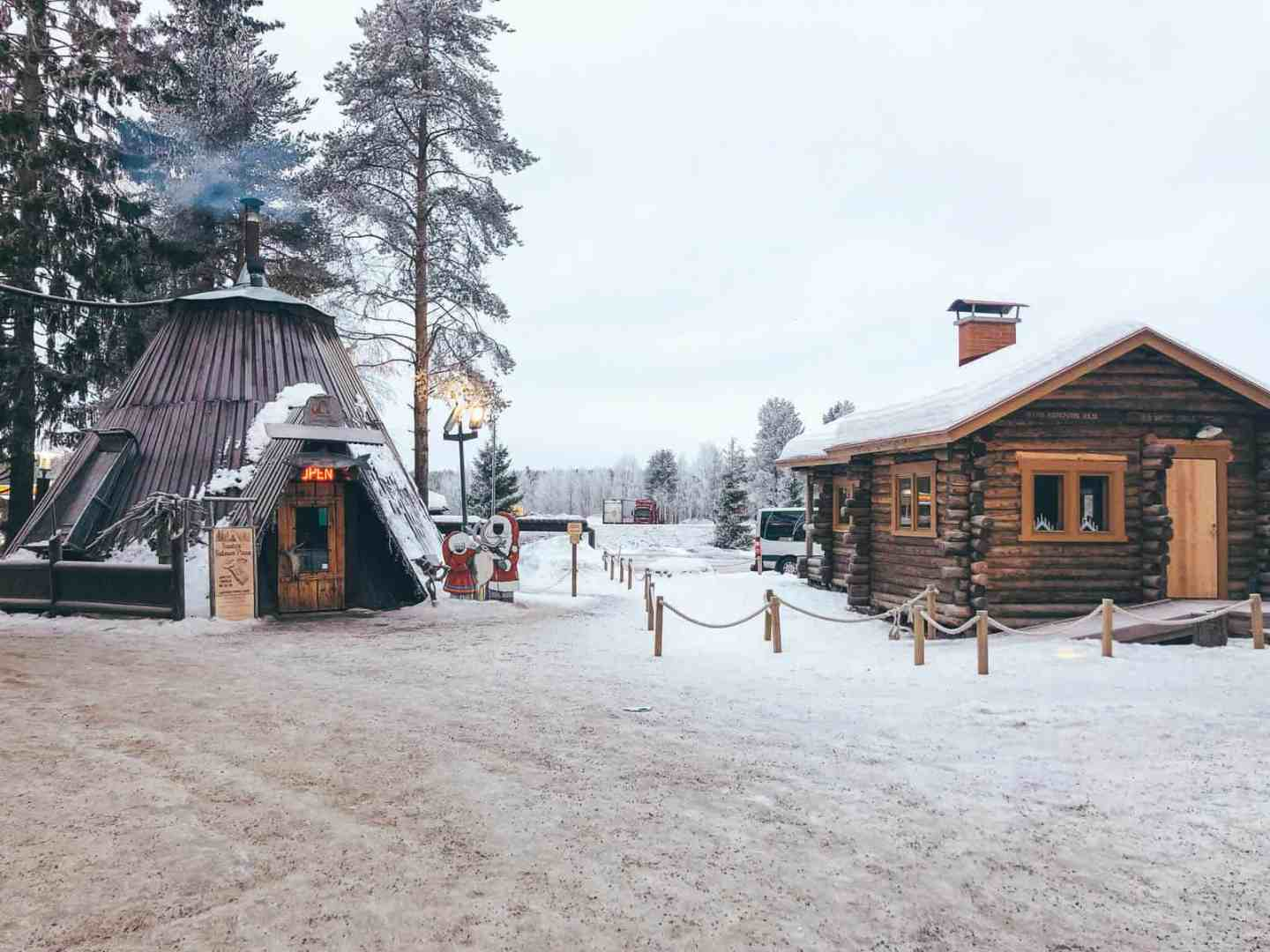 A traditional finish hut next to a log cabin