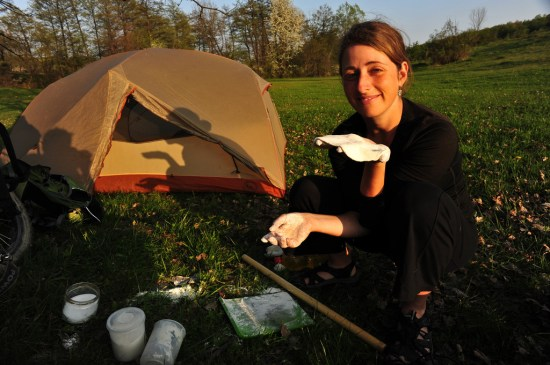 Tara wild camping and rolling out dough for dinner.