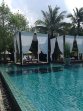 The magnificent pool and sunbeds at The Sarojin