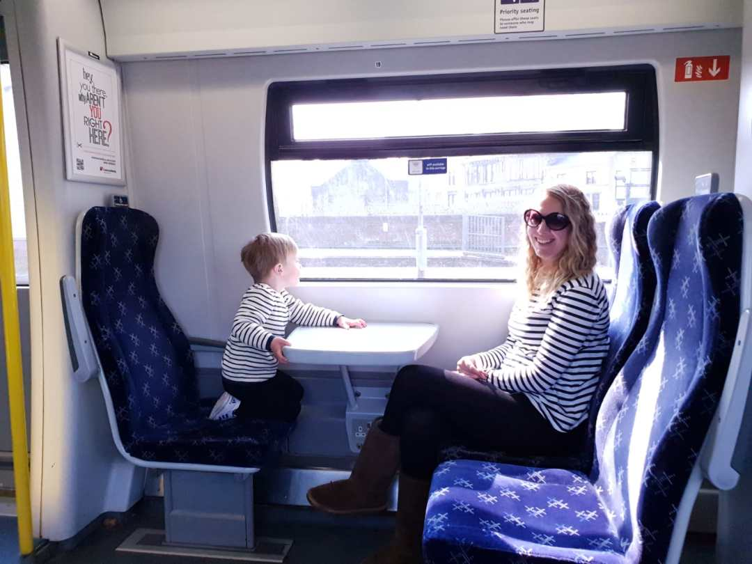 Nicola and Dexter sitting opposite each other on a train to Glasgow. Nicola looking at the camera and Dexter looking out of the window