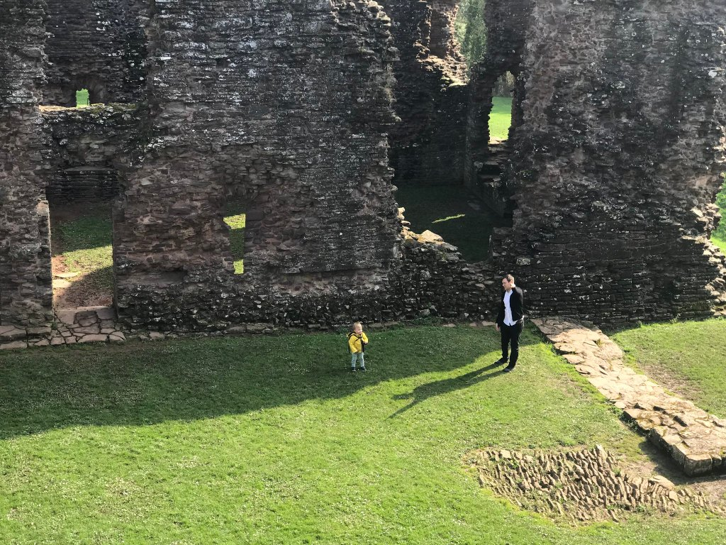 A picture tkaen from the top of Grosmont castle looking down on the ruins and Dex and Neil who are stood on the grass