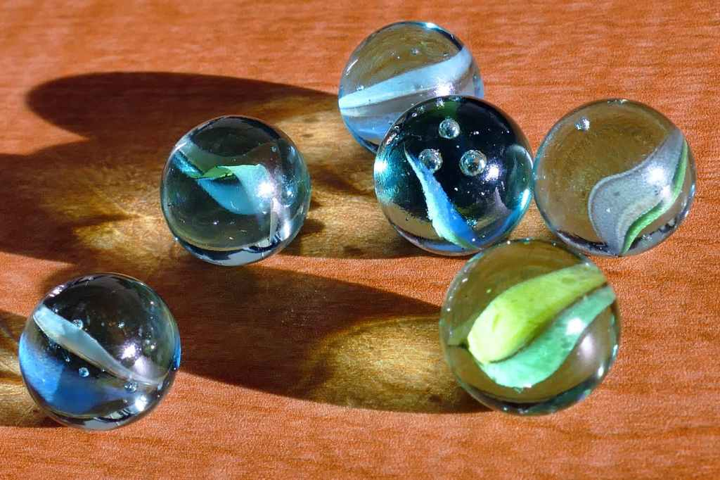 six blue and green marbles on brown surface