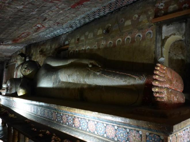A reclining Buddha statue and murals in the Rock Temple of Dambulla