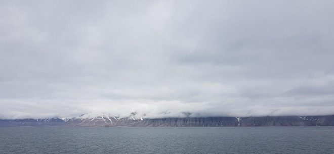 Grey clouds hanging down the mountains. Svalbard. Spitsbergen. Norway