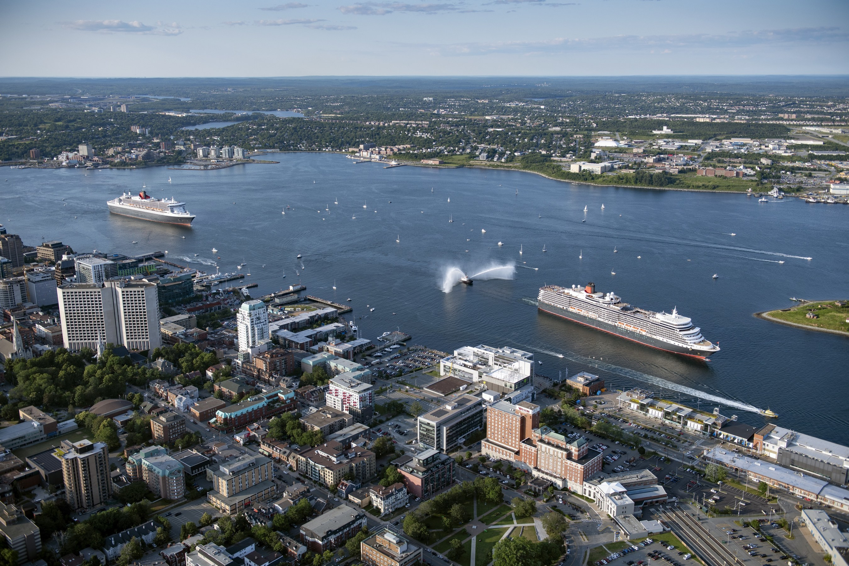 Cunard's flagship ocean liner Queen Mary 2 follows sister ship Queen Elizabeth in Halifax, Nova Scotia harbor on Friday, July 26, 2019. (Photo Credit: Steve Farmer for Cunard)
