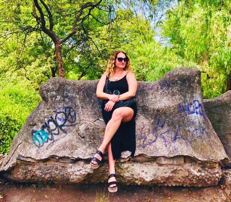 Woman wearing sunglasses and black maxi dress sitting on a rock with graffiti