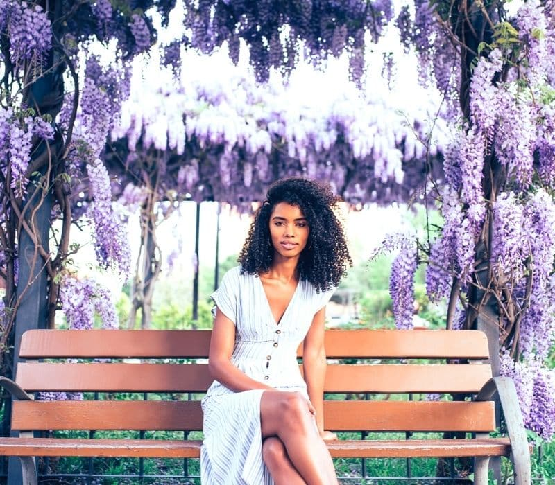 Woman sitting on a bench under purple and white flowers