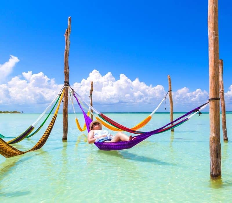 person laying in a hammock in the water in bacalar, mexico