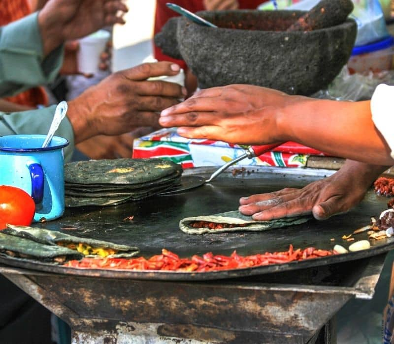 cooking a quesadilla on a traditional flat top comal cooking surface - Traveling to Oaxaca