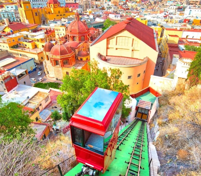 Funicular cable car going up a mountain in a colorful city