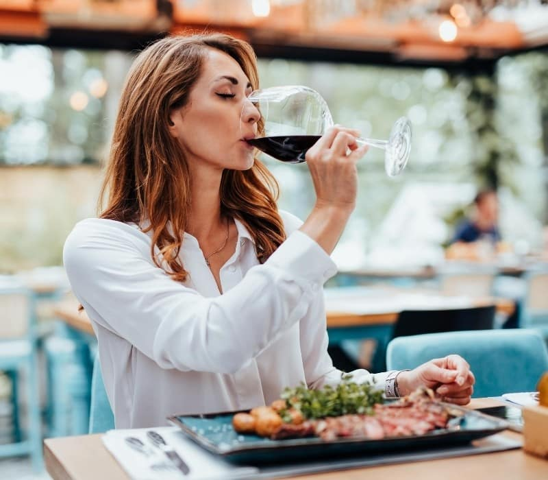 Woman eating alone at a restaurant & sipping on a glass of wine