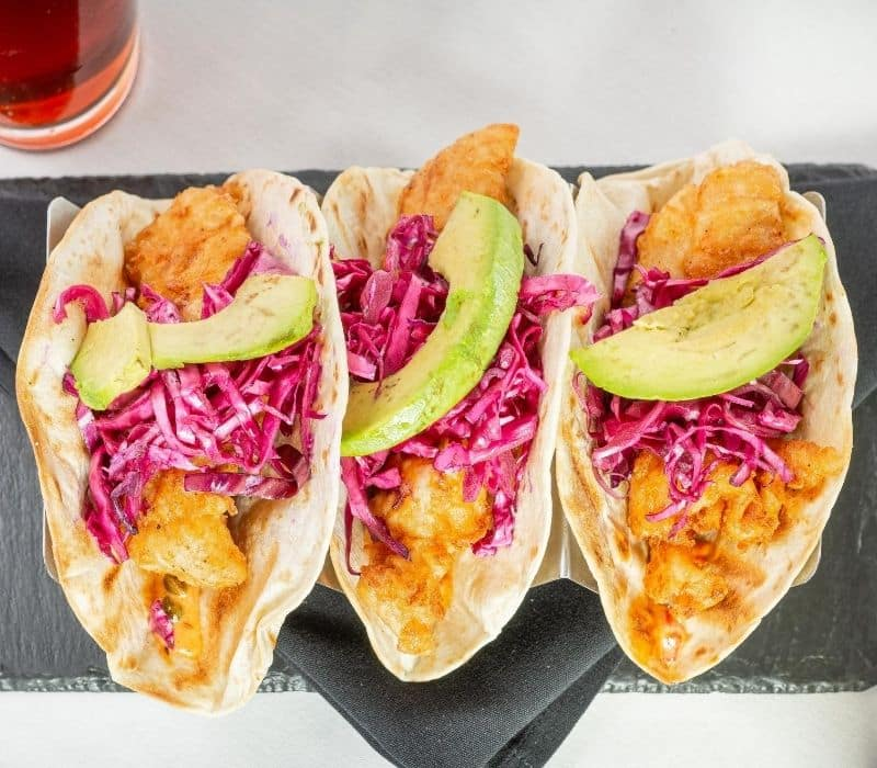 three fish tacos with purple cabbage and avocado