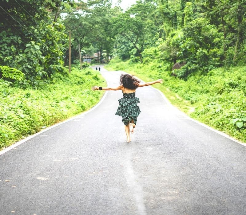 Woman in a dress running down the street with her arms extended