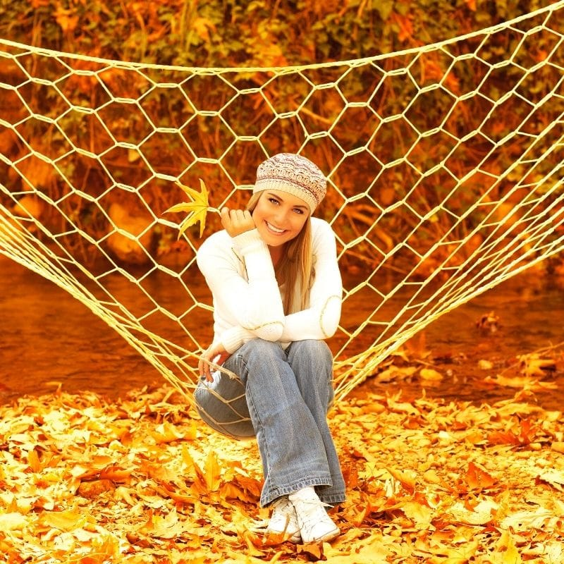 Happy woman on a hammock in fall foliage