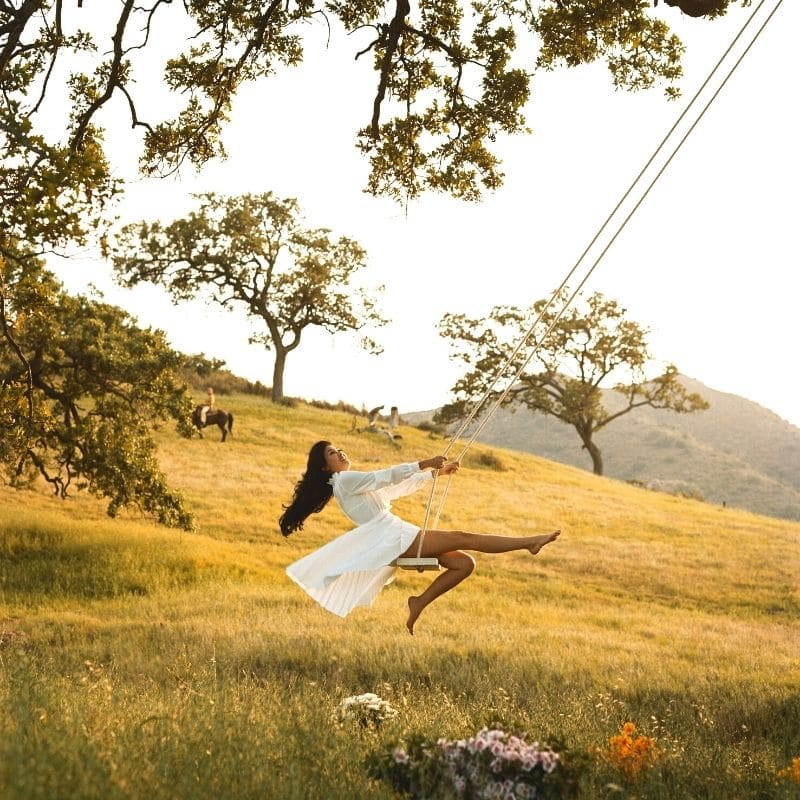 Happy woman on a swing in a mountain field