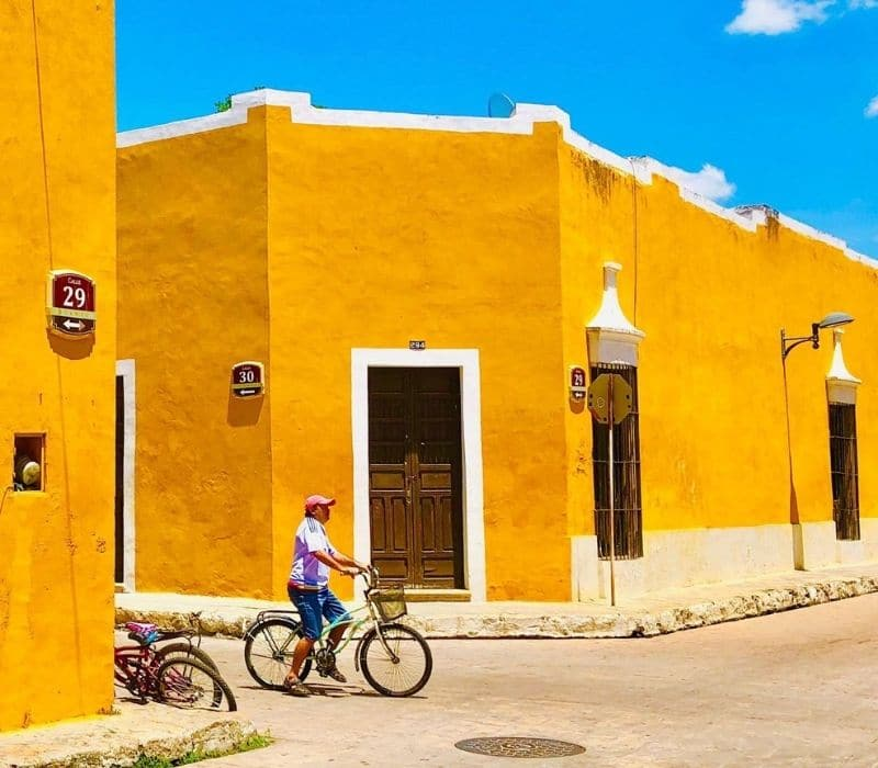colonial town with yellow walls and man on his bike in the street