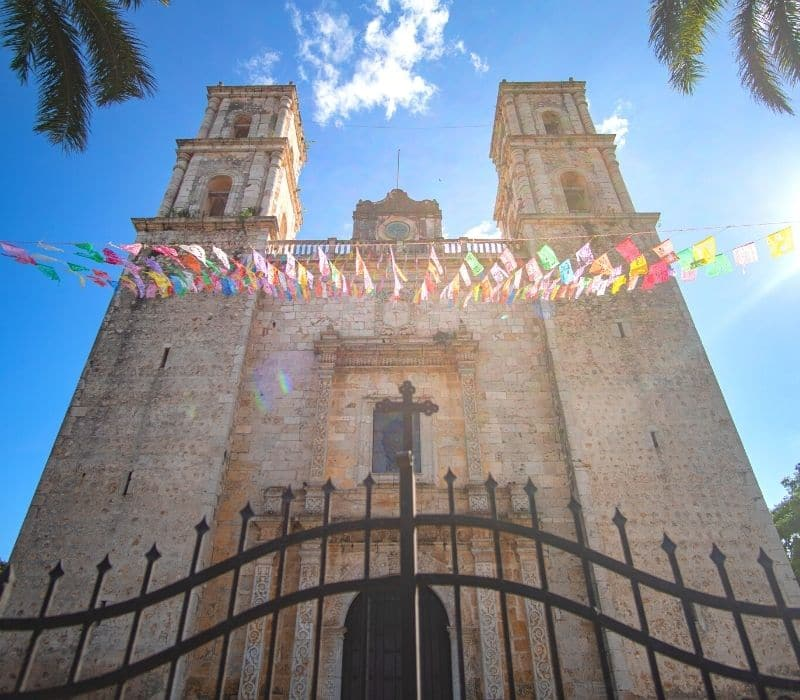 tall old stone church with colorful flags flying in front of it