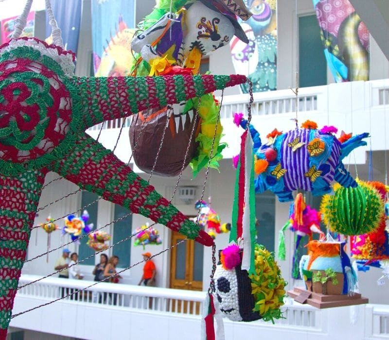 Colorful piñatas and Mexican folk art hanging from the ceiling in the Museum of Popular Art in Mexico City, one of the non-touristy things to do in Mexico City