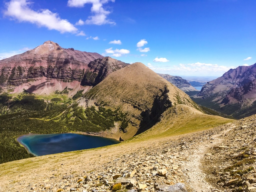 Hiking trail with lake and mountain views in Glacier National Park.