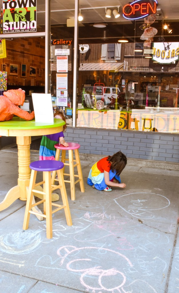 Kids drawing with chalk outside Stumptown Art Studio in Whitefish, MT