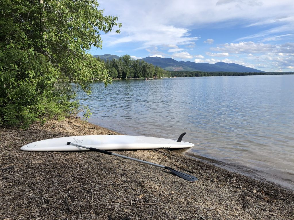 Stand up paddle board on beach in Swan Lake, Montana