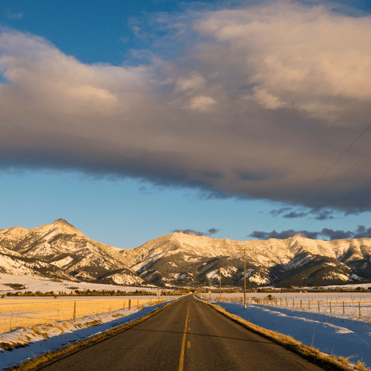 Montana Road with Snow-Capped Fields and Mountains