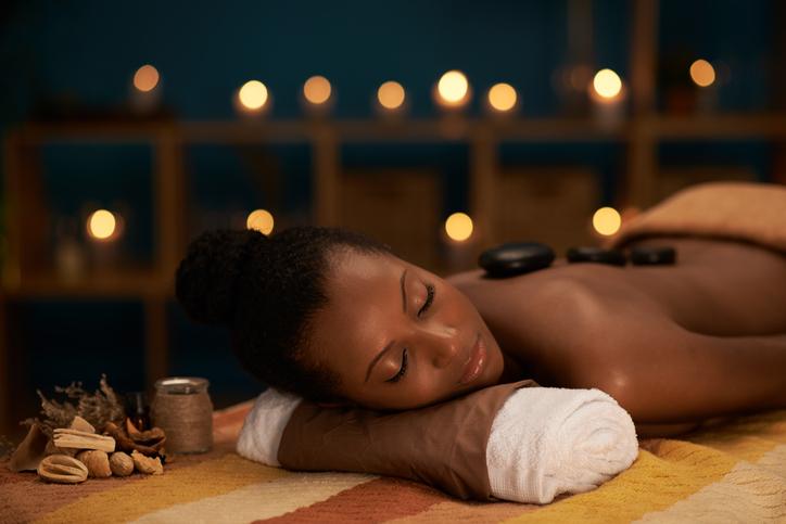 Young woman enjoying stone massage in luxury spa salon